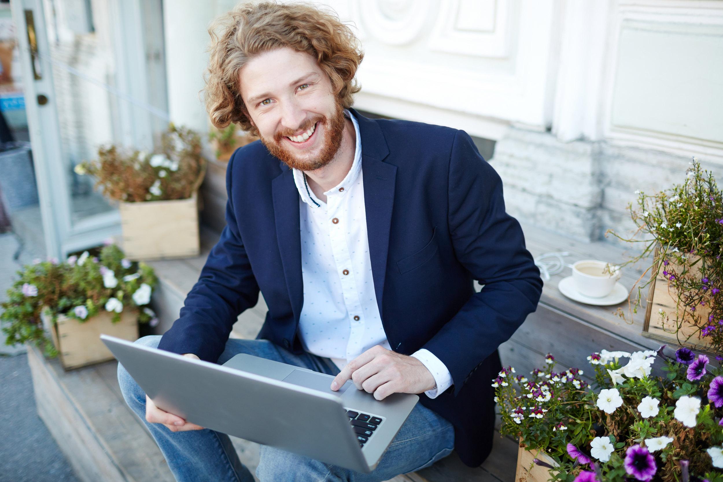 Geschäftsmann (oder Politiker) lächelt, während er am Laptop arbeitet