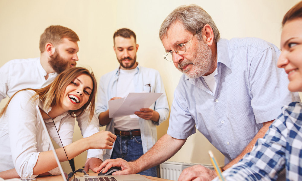 Mitarbeiter in Aktion um einen Computer versammelt